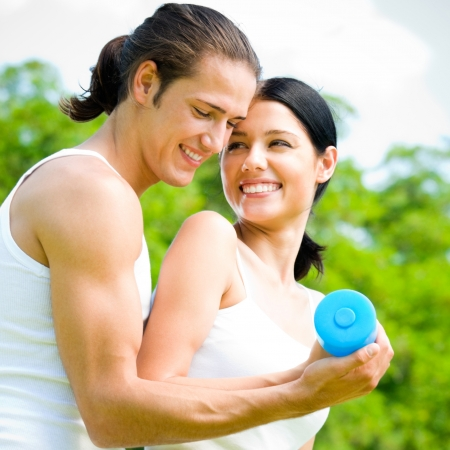 Cheerful young smiling couple with dumbbells on outdoor fitness workout photo