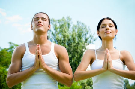 praying together: Young happy couple meditating or praying together, outdoor