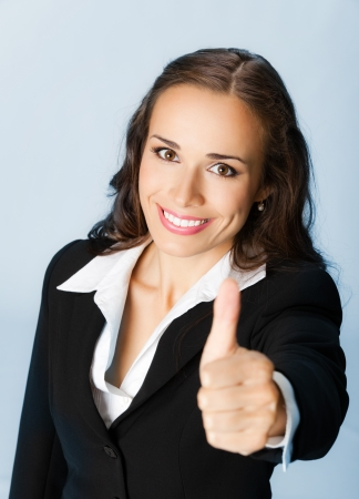 Happy smiling business woman showing thumbs up gesture, over blue background photo