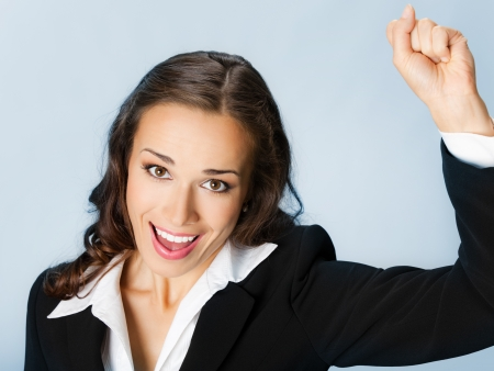 employe: Happy gesturing young cheerful smiling business woman, over blue background Stock Photo