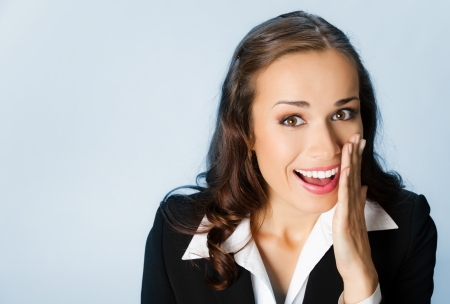 covering face: Portrait of happy young business woman covering with hand her mouth, over blue background
