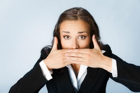 keep silent: Ritratto di donna sorpresa eccitato d'affari giovane che copre con le mani la bocca, su sfondo blu