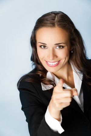 Portrait of young smiling business woman pointing finger at viewer, over blue background photo