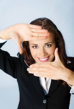 viewer: Portrait of young happy smiling business woman framing her face with hands, over blue background