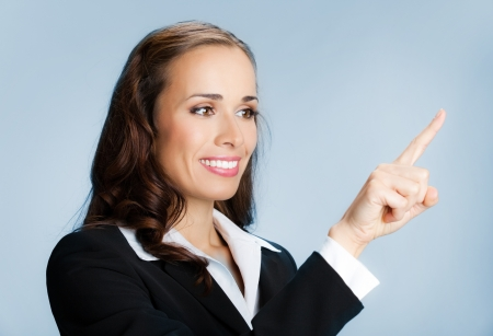 forefinger: Happy smiling young business woman showing blank area for sign or copyspase, over blue background