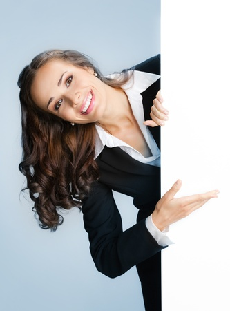 Happy smiling young business woman showing blank signboard, over blue background Stock Photo - 15243066