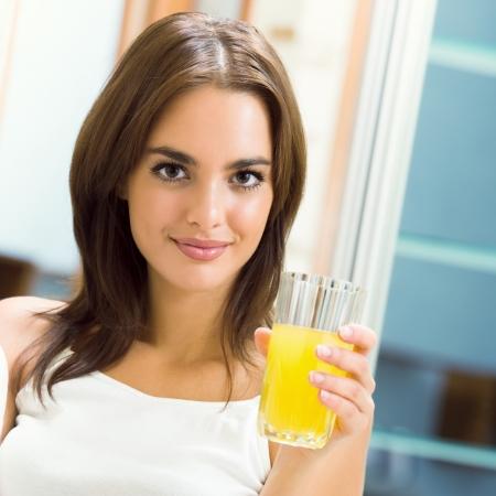 tomando jugo: Mujer alegre joven con el jugo de naranja en casa Foto de archivo