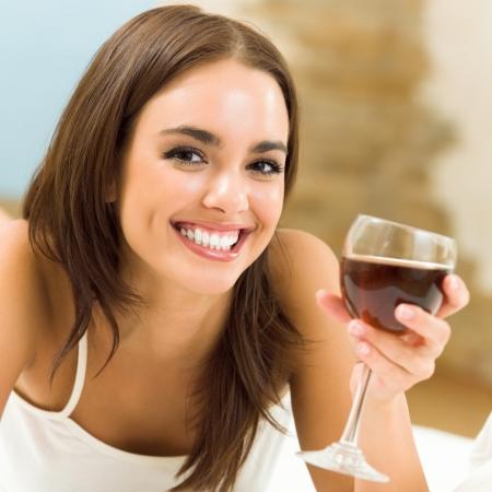 jovenes tomando alcohol: Retrato de joven sonriente feliz hermosa mujer alegre con un vaso de vino tinto