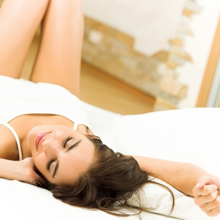 sleeping face: Young beautiful happy smiling woman waking up on bed