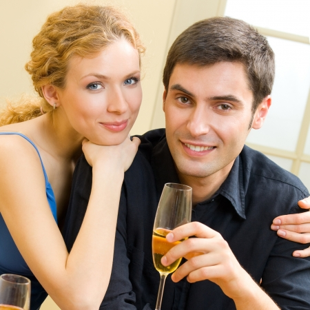 Portrait of cheerful smiling couple with champagne, indoors photo