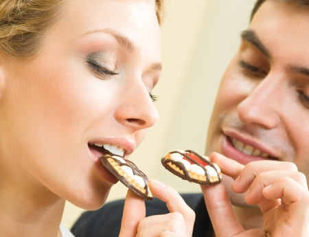 Cheerful couple eating cookies photo