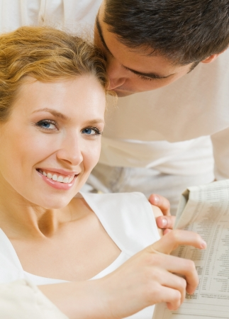 Happy couple reading newspaper together photo