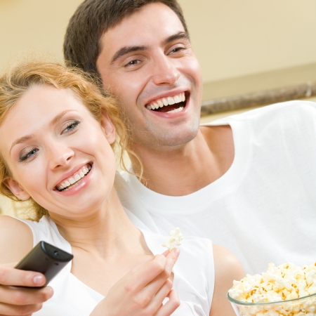 watch over: Cheerful young couple watching TV together