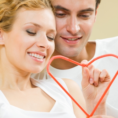 Young amorous couple with heart symbol, made with cocktail tubules, indoor photo