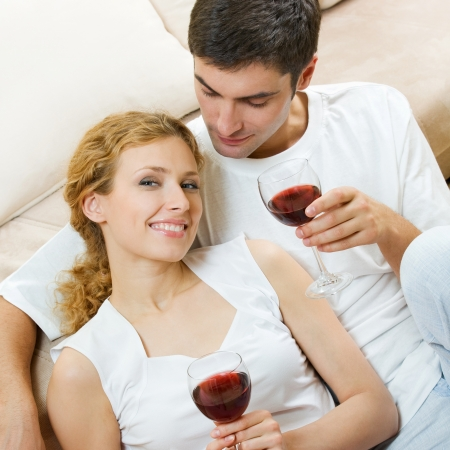 Portrait of cheerful smiling couple with glasses of red wine, indoors photo