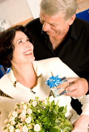 Cheerful senior couple with roses and gift indoors photo