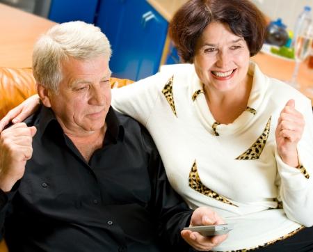 pareja viendo tv: Pareja alegre senior de ver la televisi�n juntos