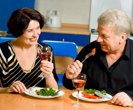 Cheerful senior couple eating at home together photo