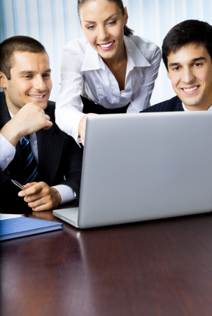 Three businesspeople working with laptop at office photo