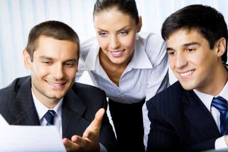 Three businesspeople working with document at office  Stock Photo - 15540630