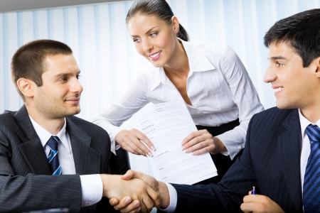 cooperate: Three businesspeople handshaking with document at office