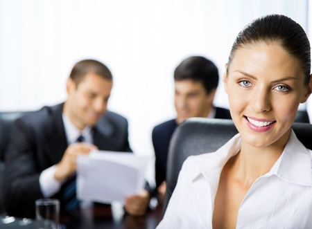 Portrait of happy smiling businesswoman and colleagues on background, at office photo