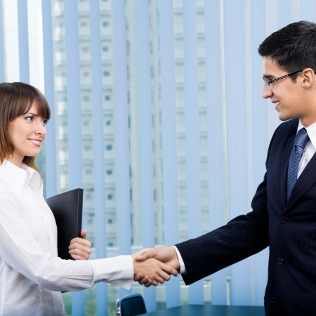 Cheerful businesspeople, or business person and client, handshaking Stock Photo