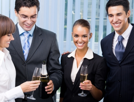 Cheerful successful business team celebrating with champagne at office photo
