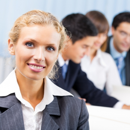 associates: Portrait of happy smiling businesswoman and colleagues on background, at office