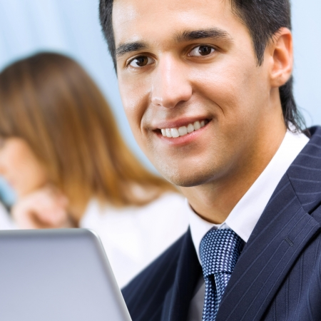 social worker: Portrait of successful happy smiling business man working with laptop at office Stock Photo