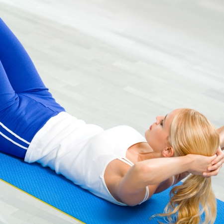 Young woman in sports wear doing fitness exercise, indoors photo