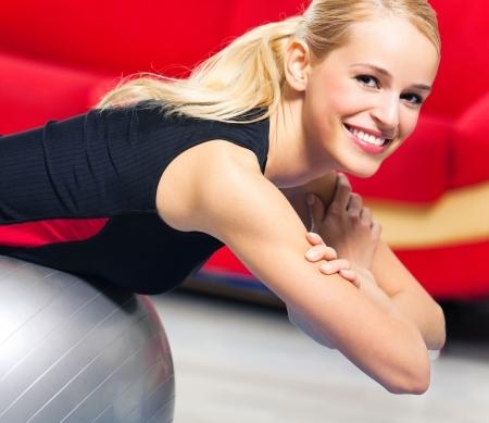 pilate: Jeune femme heureuse faire des exercices de remise en forme avec ballon en forme � la maison