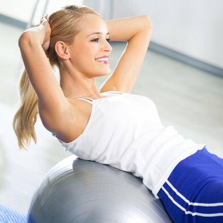 Young happy woman doing fitness exercises with fit ball at home photo