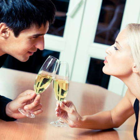 Young cheerful amorous couple with champagne on romantic date or celebrating at restaurant photo