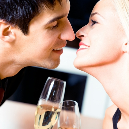 Young cheerful amorous kissing couple with champagne on romantic date or celebrating at restaurant photo