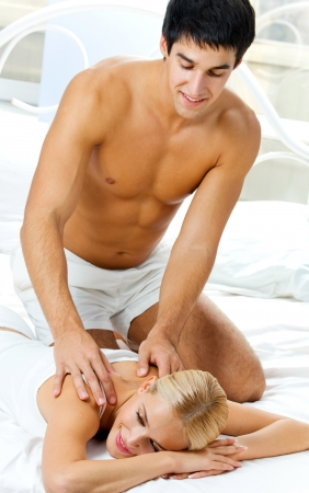 Cheerful young couple making massage at home photo
