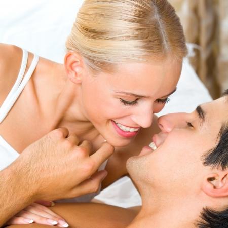 Joven pareja bes�ndose en la cama alegre atractivo photo