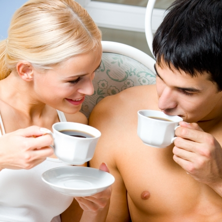 Cheerful couple with cups of coffee, indoor photo