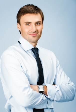 Portrait of happy smiling young business man, over blue background photo
