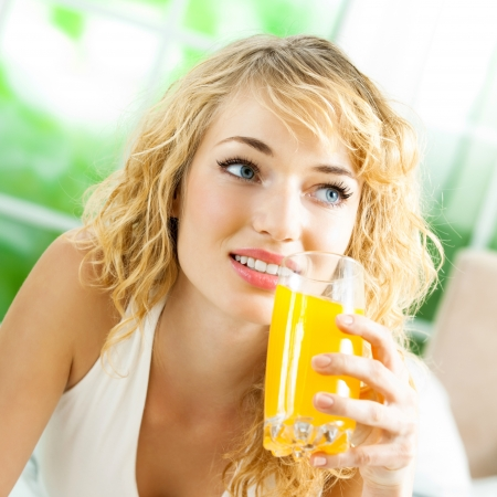 Portrait of happy smiling young beautiful blond woman drinking orange juice photo