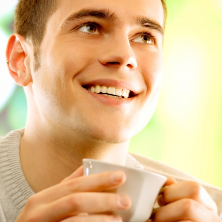 hombre tomando cafe: Hombre joven sonriente feliz con la taza de café, al aire libre, Foto de archivo