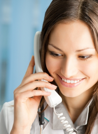 Portrait of happy smiling cheerful young female doctor on phone, at office Stock Photo - 15920614