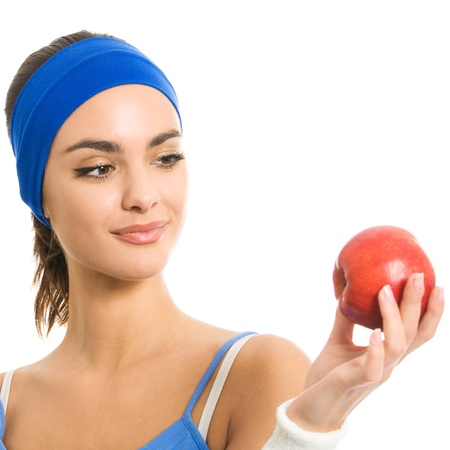 Young cheerful woman in sports wear with apple, isolated over white background photo