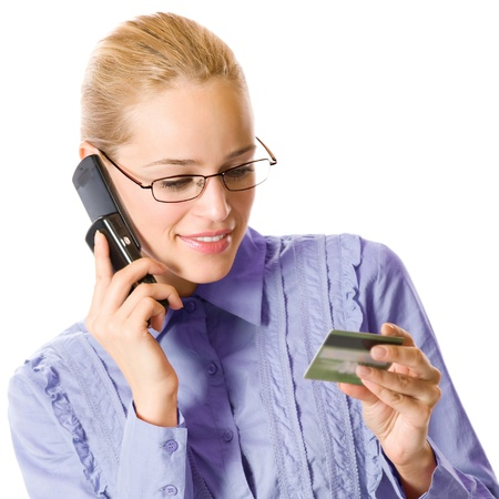 Young happy smiling business woman with plastic card, on cellphone, isolated over white background photo