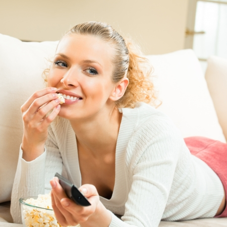 Portrait of young blond happy smiling woman watching TV at home photo