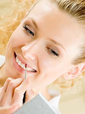 wellfare: Cheerful smiling woman applying lipstick