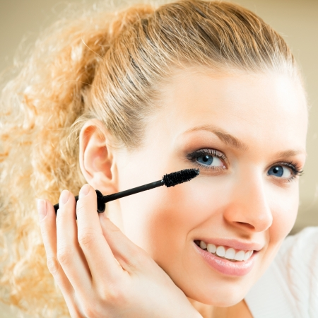 Cheerful woman applying mascara with lash brush photo