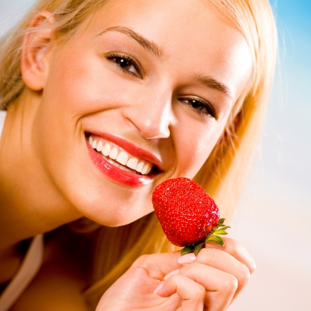blondy: Young beautiful woman with strawberry on beach