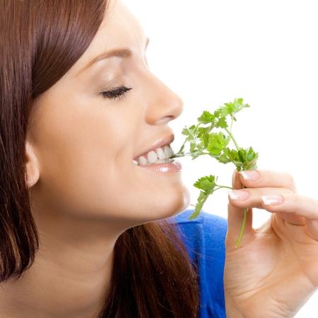 potherbs: Alegre mujer comiendo hierbas arom�ticas, aislado sobre fondo blanco Foto de archivo