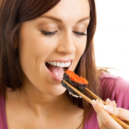over eating: Portrait of cheerful beautiful woman eating sushi roll with chopsticks, isolated over white background Stock Photo